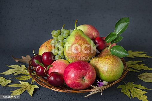1020586746istockphoto Composition of ripe fruits and yellow autumn leaves on a black background. Harvest concept 840324822