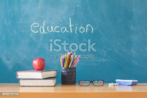istock Composition of stationery ,books and an red apple on the desk,The background is blackboard, educational concepts 970272110