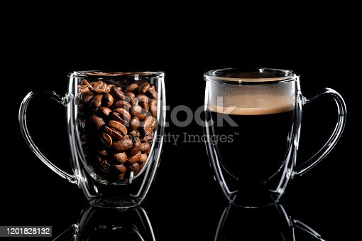 composition of two cups with coffee on a black background. left side cup with coffee bean side view, right side cup with finished coffee side view. Black background.