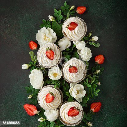 istock Composition of vanilla cupcakes with fresh strawberry   and white roses flowers on dark green  background 831559686