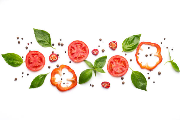 Composition of vegetables, herbs and spices on white background Food art. Creative composition of cut pepper, tomato, basil leaves and spices on white background, top view basil stock pictures, royalty-free photos & images