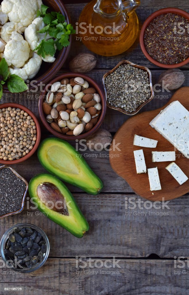 Composition of vegetarian products containing unsaturated fatty acids Omega 3 - nuts, hemp, chia, flax, avocado, soybeans, cauliflower, pumpkin seeds, tofu, dill, vegetable oil. Top view. Healthy food stock photo