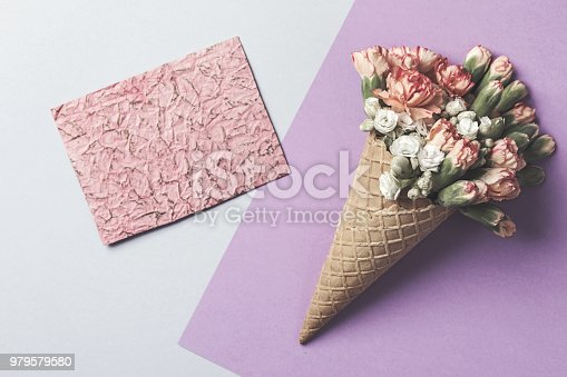 680461500istockphoto Composition of waffle cone with spring cloves bouquet on purple and blue the background with greetings red card . Flat lay, top view. Place for inscription. Mothers day, anniversary, greetings. 979579580