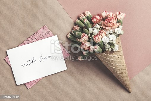 680461500istockphoto Composition of waffle cone with spring cloves bouquet on the brown and pink vintage background with greetings card . Flat lay, top view. Place for inscription. Mothers day, anniversary, greetings. 979579712