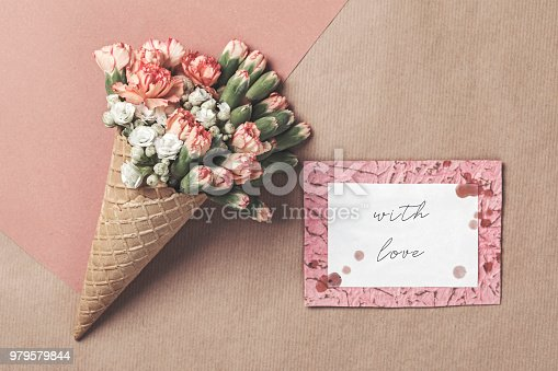 680461500istockphoto Composition of waffle cone with spring cloves bouquet on the brown and pink vintage background with greetings card . Flat lay, top view. Place for inscription. Mothers day, anniversary, greetings. 979579844