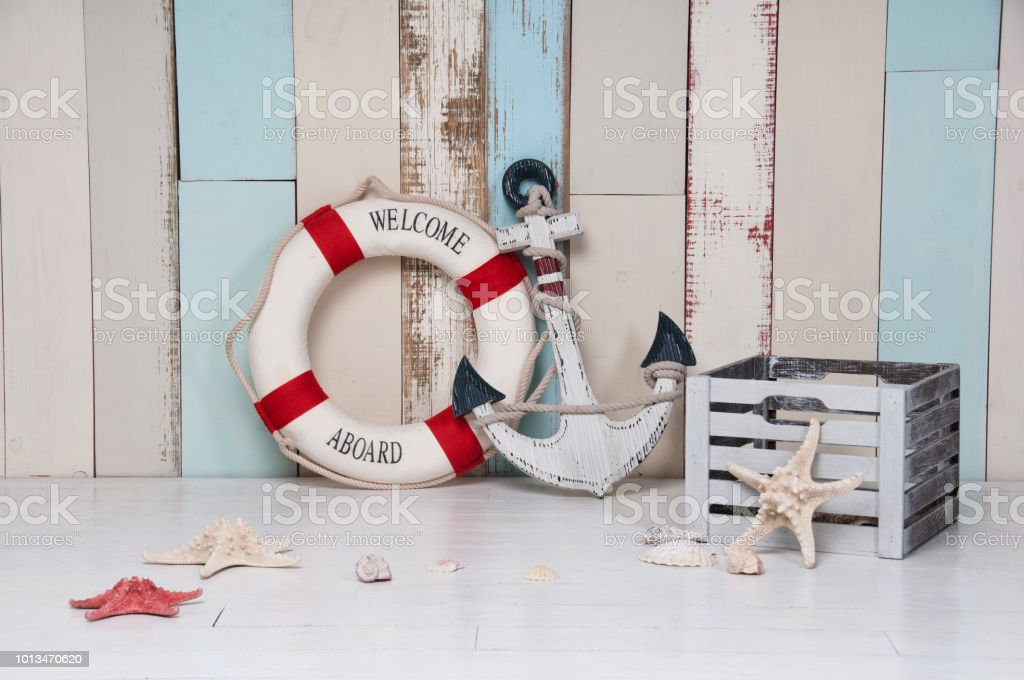 Composition on a marine theme with an anchor and life buoy, seashells and starfish on a wooden background стоковое фото
