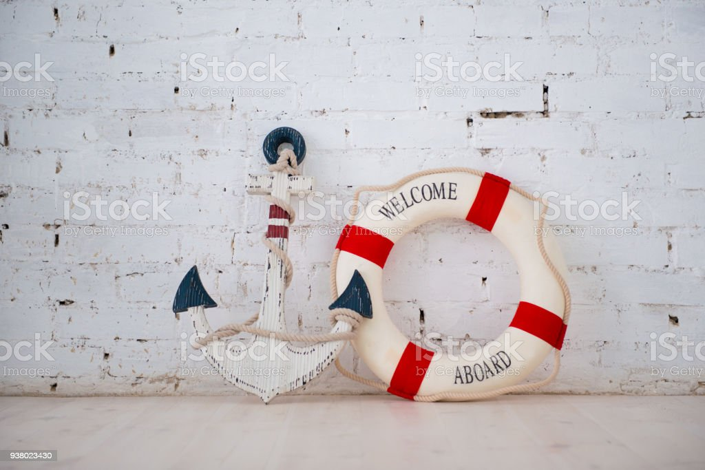 A composition on a sea theme with an anchor and life ring on a white brick wall стоковое фото