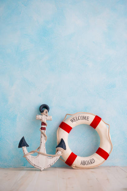 A composition on a sea theme with an anchor and lifebuoy on a blue wall stock photo
