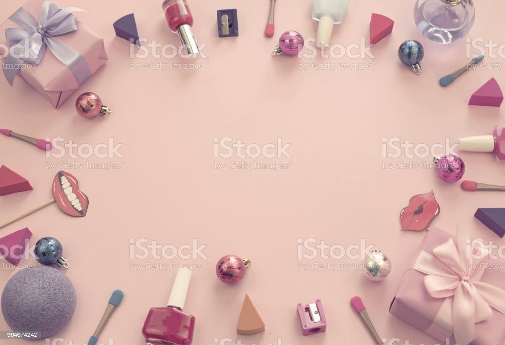 composition set of decorative cosmetics nail Polish lipstick sponge sharpener box gift ribbon satin bow background pink. royalty-free stock photo