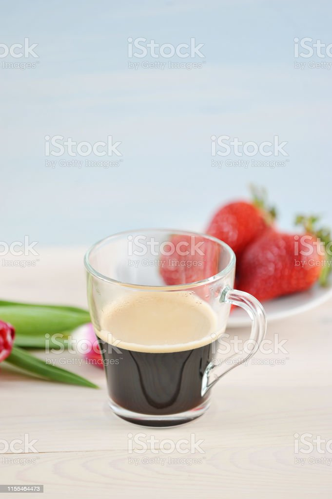 Composition with a cup of coffee and flowers. In a transparent cup of...