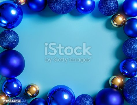 Composition with blue and gold Christmas balls on a blue background with copy space. Christmas frame.