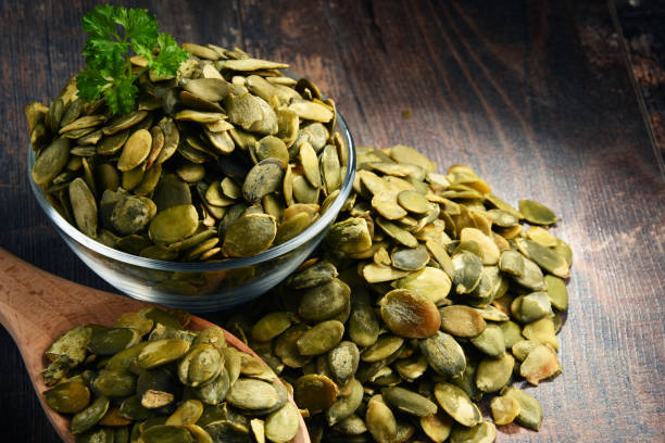 Composition with bowl of pumpkin seeds on wooden table stock photo