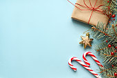Composition with Christmas gift box, fir tree branch, candy canes.