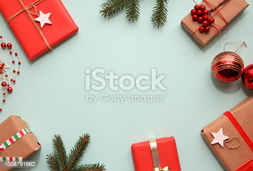 istock Composition with Christmas gift boxes, fir tree branches and decorations on blue background. 1058791662