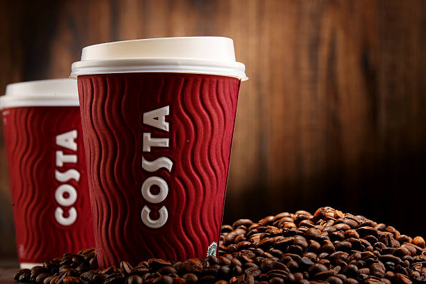 Komposition mit Tasse Kaffee und Bohnen mit Kaffee von Costa – Foto