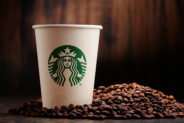 Komposition mit Tasse Starbucks-Kaffee und Bohnen – Foto