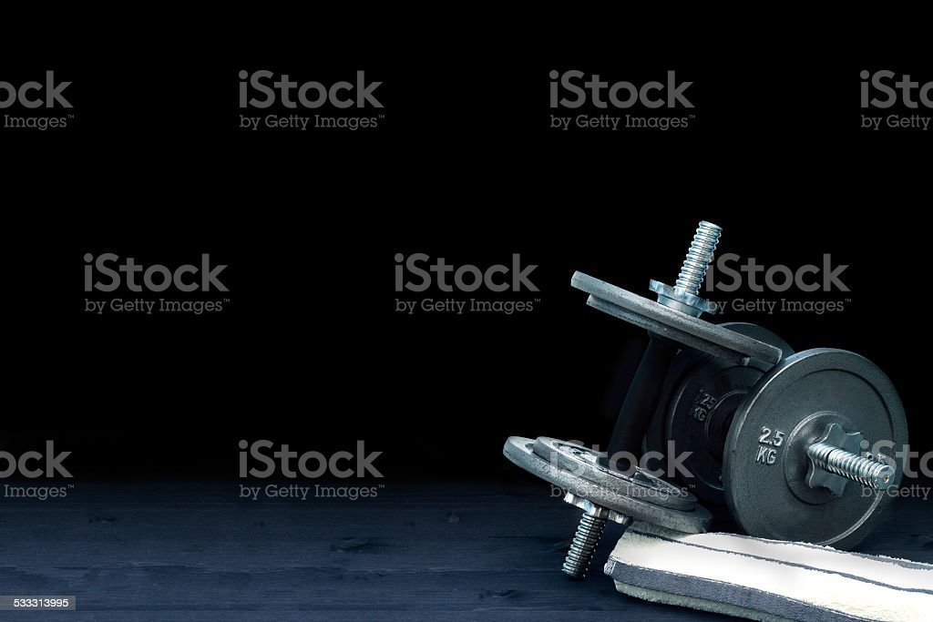 Composition with dumbbells and towel on wooden board stock photo