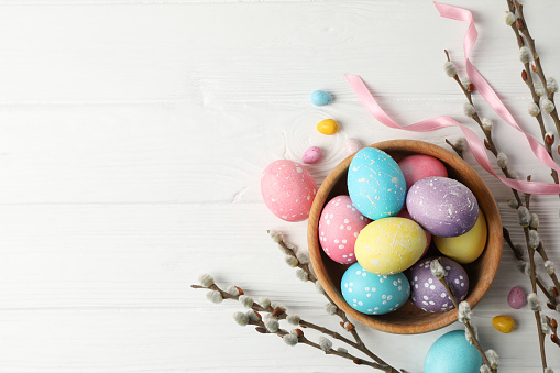 Composition with Easter eggs on white wooden background, space for text