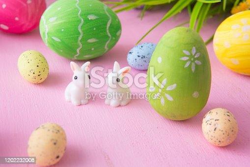 Composition with Easter eggs with rabbits or hare toys and flowers on a pink wooden background.