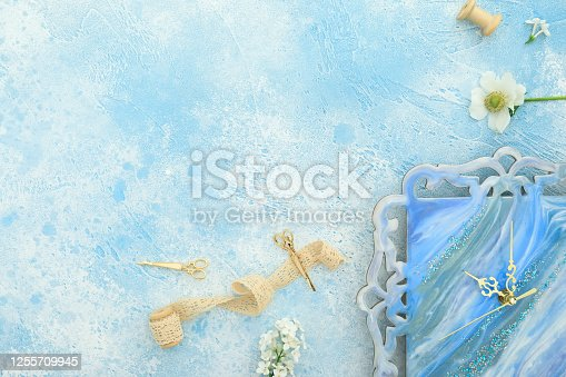Composition with flowers, resin art watch, tassel, scissors and pen on blue background. Flat lay, top view