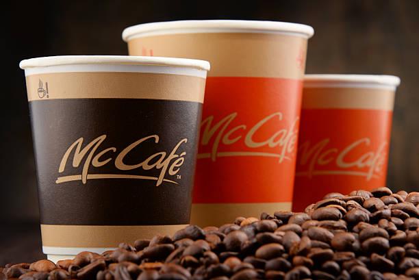 композиция с mccafe чашкой кофе и кофейных зерен - mcdonalds стоковые фото и изображения