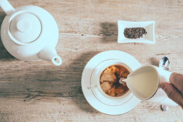 Composition with tea cup, tea pot and person pouring milk on wooden background, flat lay stock photo