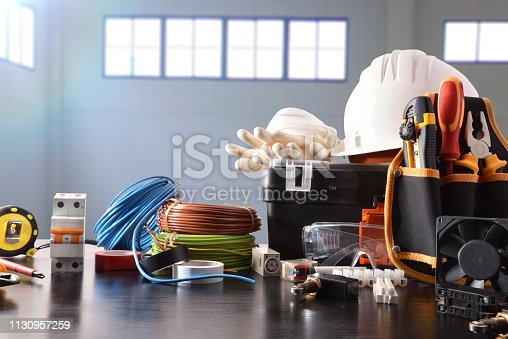 Composition with tools and electrical equipment on black table and industrial ship background. Horizontal composition. Front view.