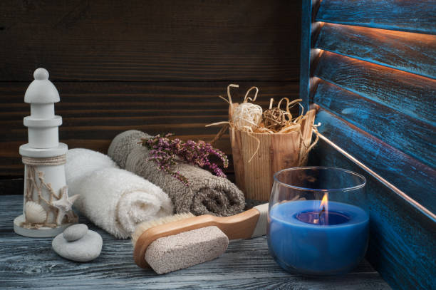 spa-komposition mit handtüchern, pinsel, zündete die kerze an - badezimmer rustikal stock-fotos und bilder