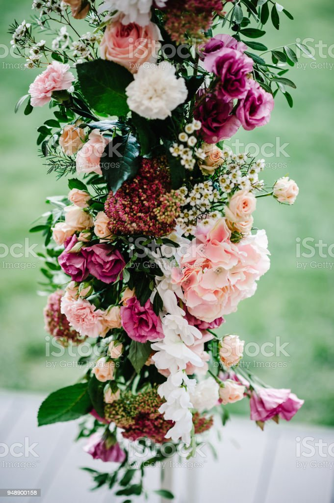 Compositions of flowers decorated with pink hydrangeas, roses, white carnations and greens, which is located stands on arch for wedding ceremony. wedding decor. stock photo