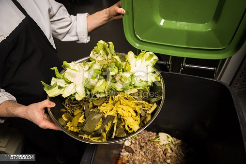 Chef emptying vegetable scraps into a composting bin