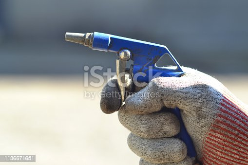 Compressed air gun in the hand of a worker.