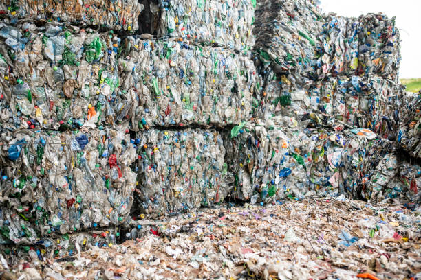 Compressed Paper and Plastic Stacked at Recycling Facility Close-up of multicolored bundles of compressed paper and plastic stacked outdoors at recycling facility. social responsibility stock pictures, royalty-free photos & images