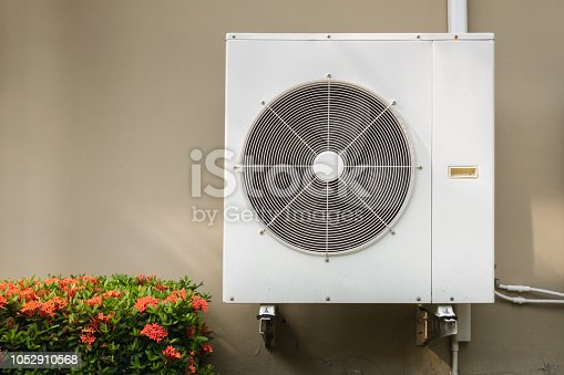 871063730istockphoto Compressor air conditioning system installation embedded on wall of building. 1052910568