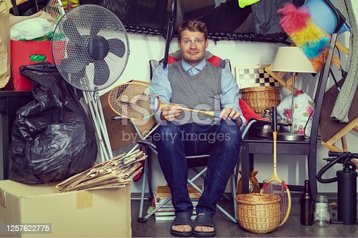 istock compulsive hoarding disorder concept - man hoarder with stuff piles sitting in the room 1257622775