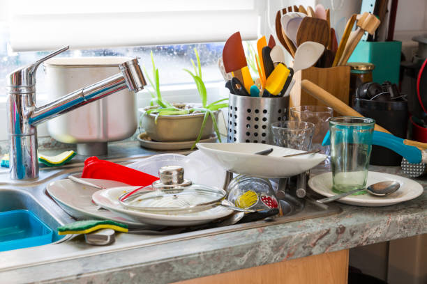 Compulsive Hoarding Syndrom - messy kitchen with pile of dirty dishes stock photo