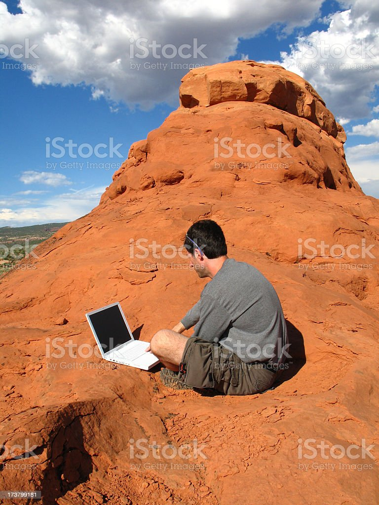 Compute Anywhere: Man Sits with Laptop Computer on Desert Red-Rock royalty-free stock photo