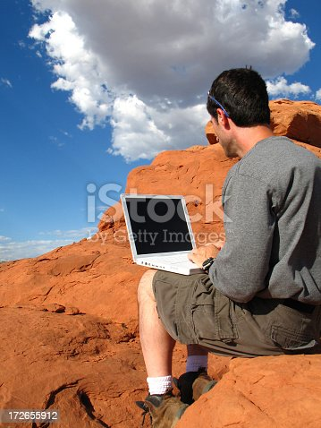 This color photo, a concept for computing anywhere, shows a dark-haired man in short pants and long-sleeved shirt with a white laptop computer sitting on a red-rock formation in the eastern Utah desert south of Moab, Utah. The image has a dramatic blue sky with fluffy, white clouds.