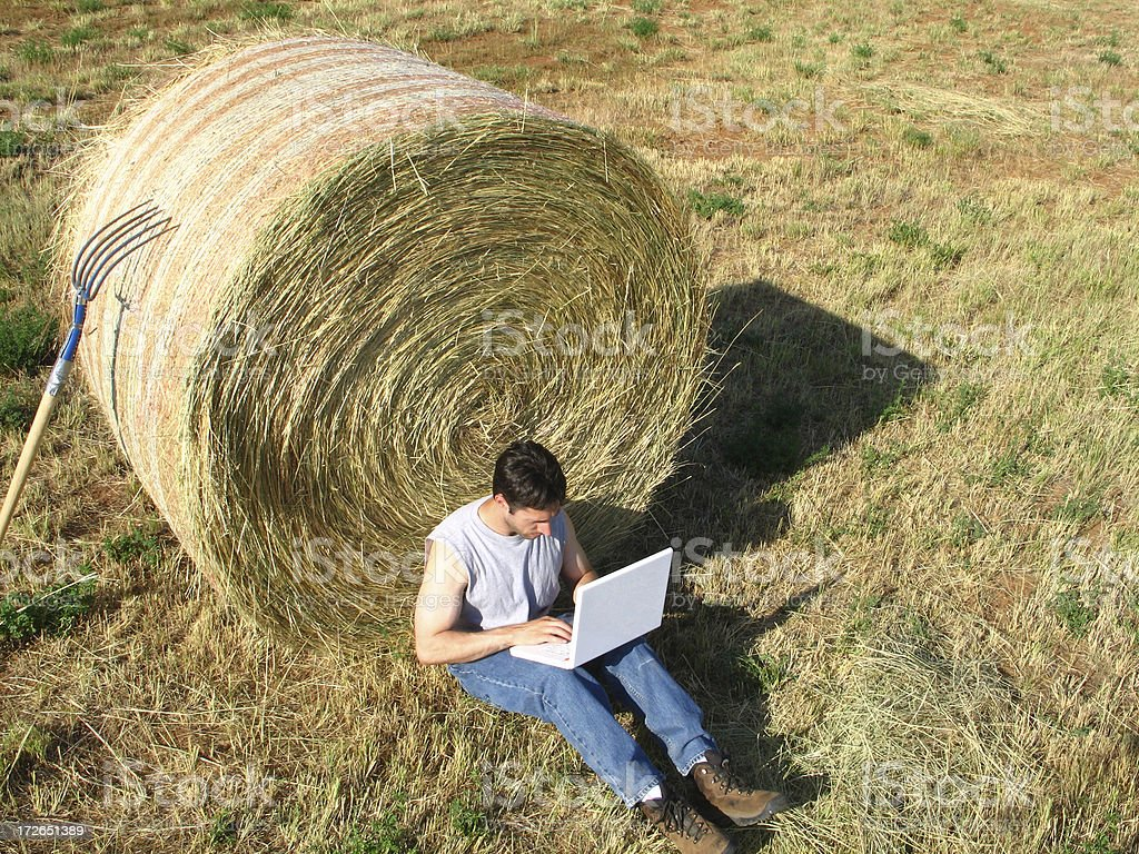 Compute Anywhere: Man with Laptop Computer Sits by Round Hay-Bale royalty-free stock photo
