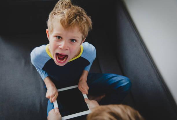 Computersucht-Vater nimmt Touchpad von wütendem Kind – Foto