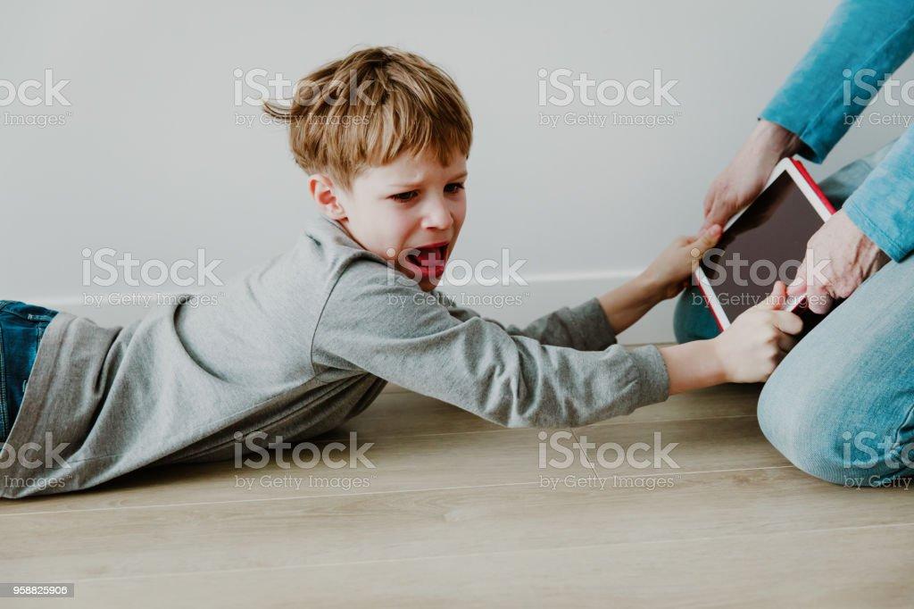 怒っている子供からタッチパッドのコンピューター中毒父撮影 ストックフォト