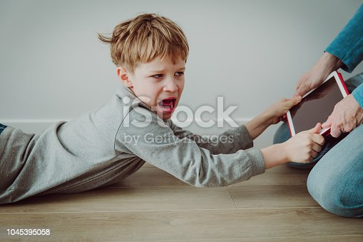 istock computer addiction- father taking touch pad from angry shouting child 1045395058