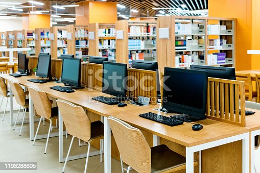 Computer and bookshelves in modern library.