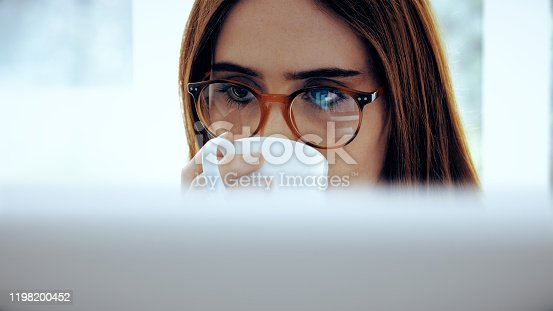 Attractive young woman drinking coffee while studying a computer screen, details of data and graphs reflect in her glasses.