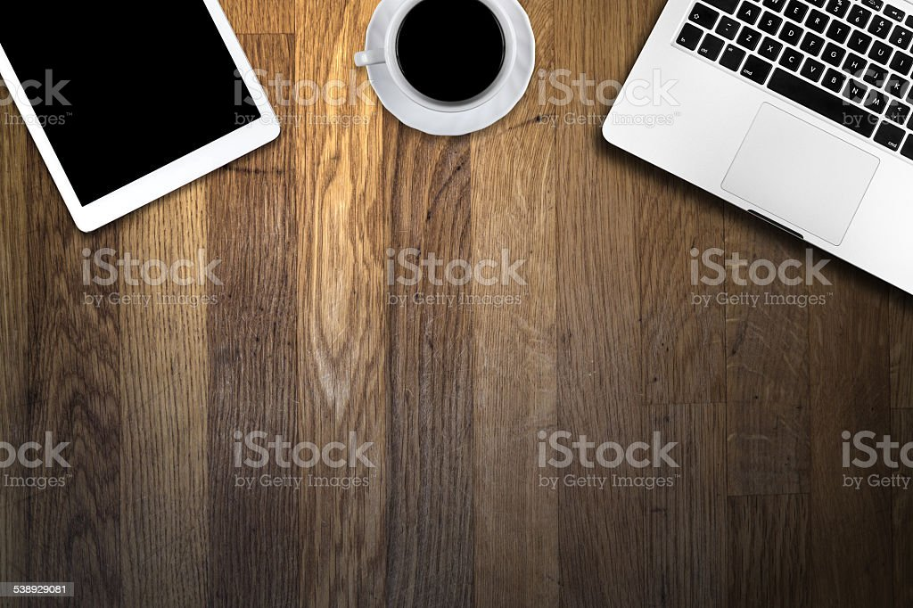 computer and cup of coffee on wooden table stock photo