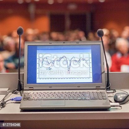 854811490 istock photo Computer and microphone on rostrum at business event. 612754046
