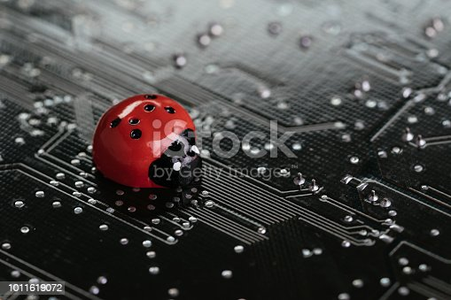 istock Computer bug, failure or error of software and hardware concept, miniature red ladybug on black computer motherboard PCB with soldering, programmer can debug to search for cause of error 1011619072
