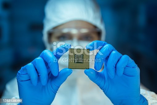 Engineer analyzing computer chip in laboratory