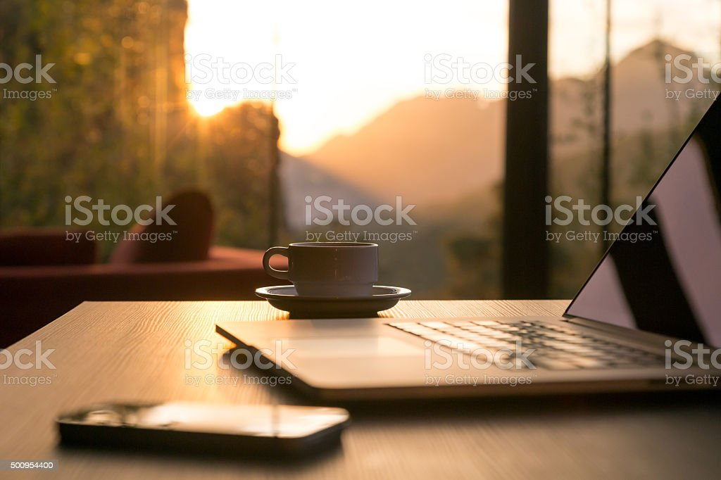 Computer Coffee Mug Telephone on black wood table sun rising royalty-free stock photo