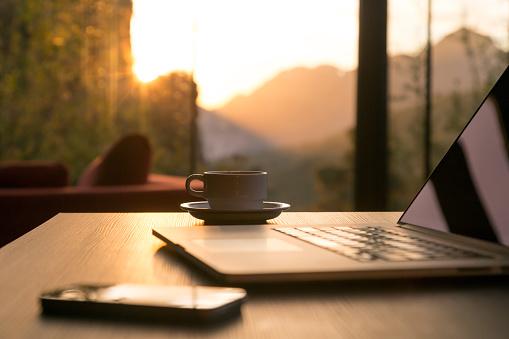 Computer Coffee Mug Telephone On Black Wood Table Sun Rising Stock Photo - Download Image Now