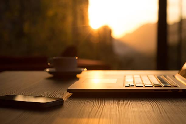 Computer, Kaffeebecher Telefon auf Schwarz Holz Tisch aufgehenden Sonne – Foto